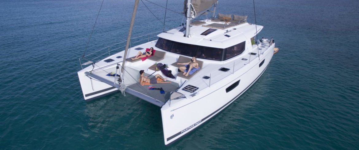 Catamaran charter yacht on anchor. Lounging on deck.