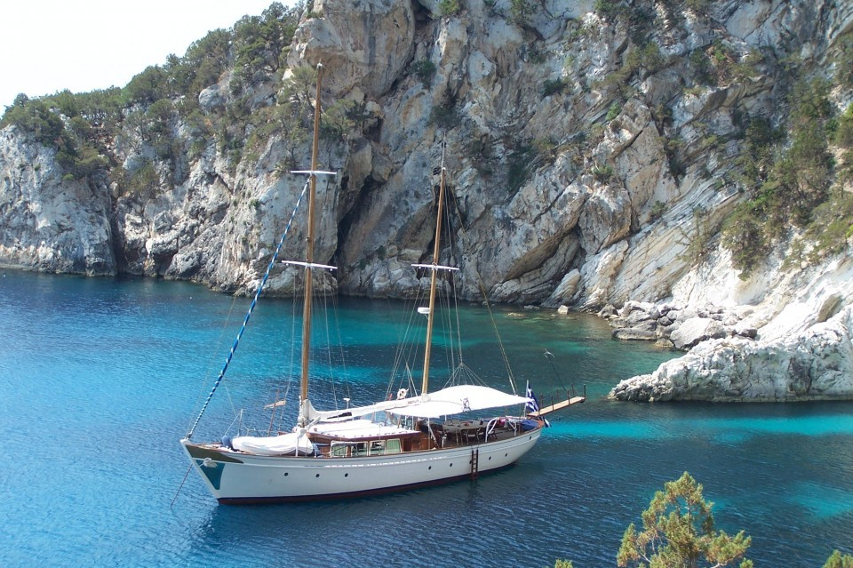 A motor sailing charter yacht anchored in front of the rock. Beautiful clear swim water in Greece.
